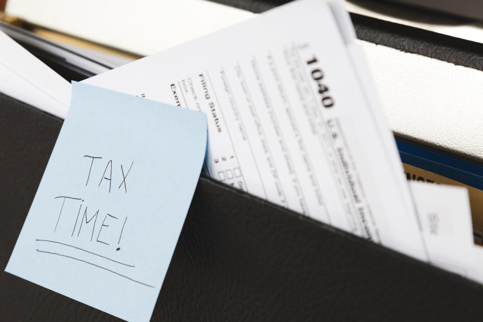 blue post-it note saying tax time! stuck on folder with 1040 income tax form in the background