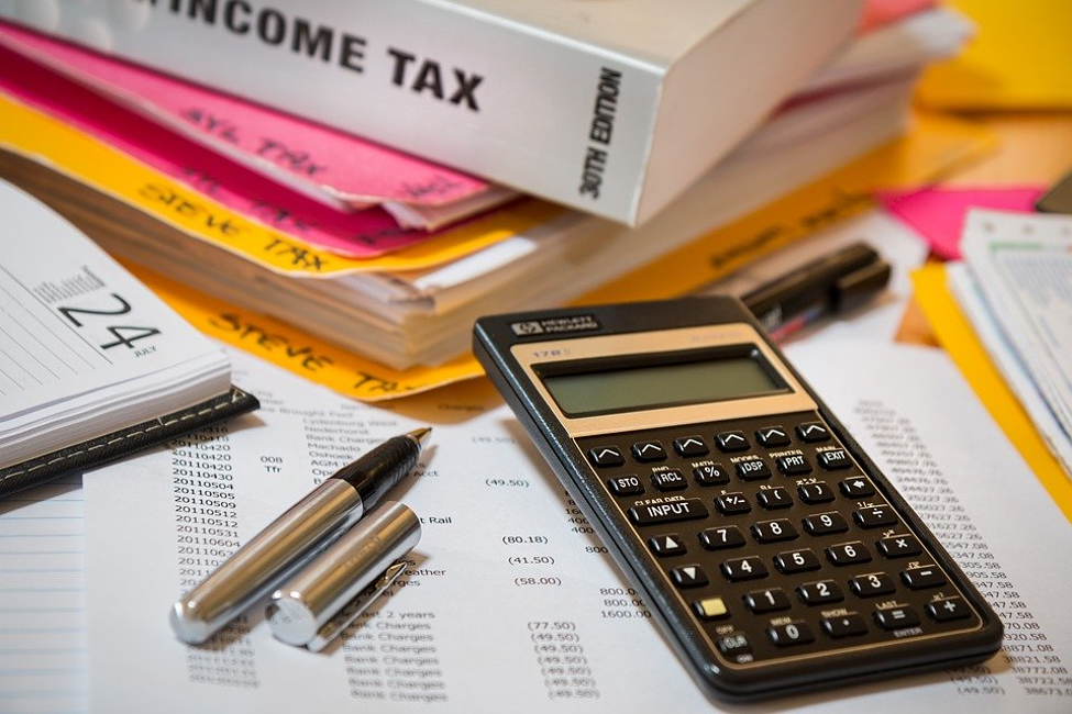 calculator on top of paper next to uncapped pen file folders and book on income tax
