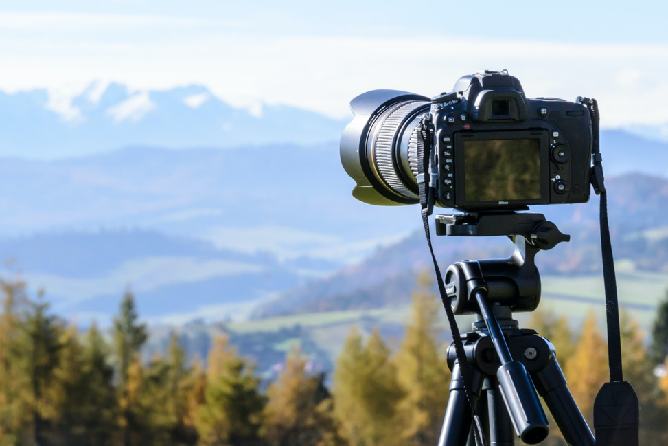 person taking pictures of mountains to earn money from home