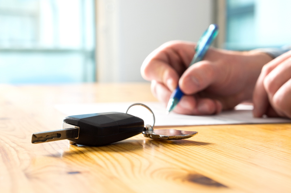 Person signing a bad credit auto loan next to car keys