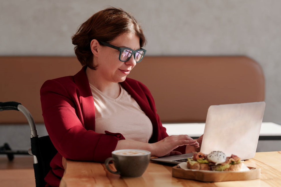 smiling woman in glasses sitting in wheelchair next to wooden table with snacks coffee mug and open laptop looking up quick installment loans online