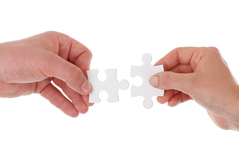 two hands holding interlocking white puzzle pieces next to each other in front of white background