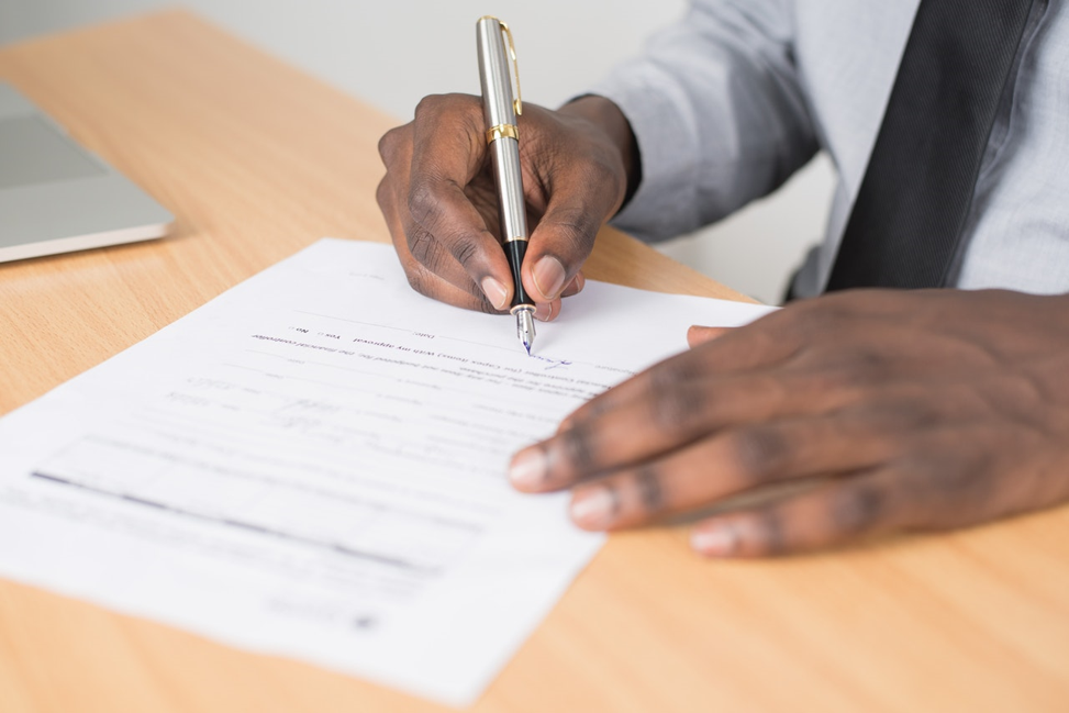 person signing contract for emergency loans online