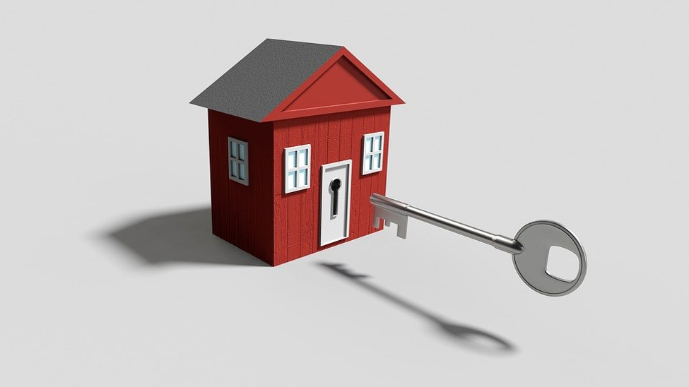 silver key lining up to keyhole on small red house with grey roof white doors and white windows