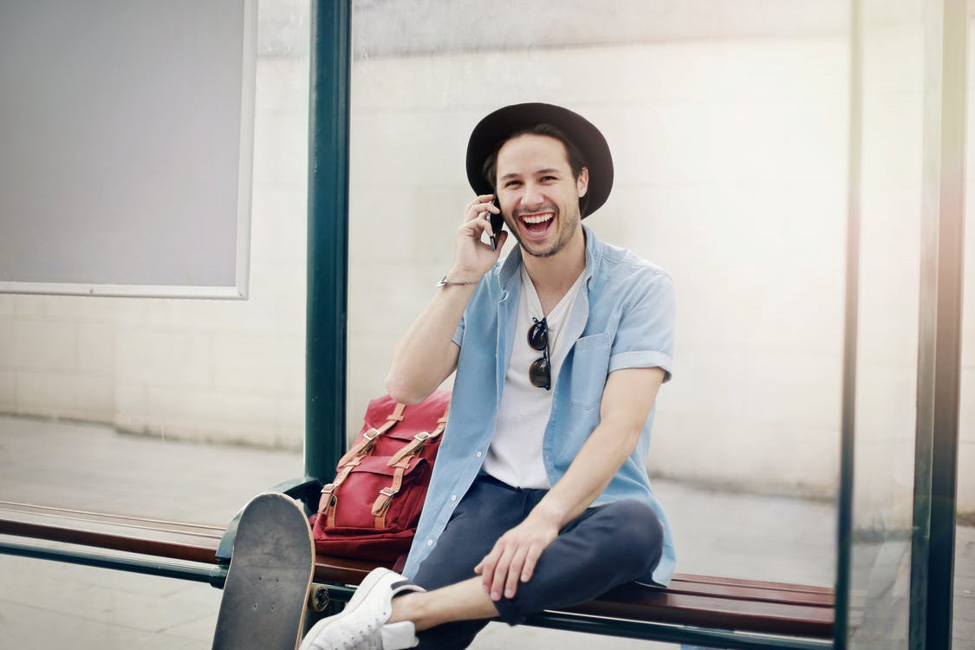 smiling man in black hat holding smartphone to right ear while sitting on a bench next to red backpack and skateboard