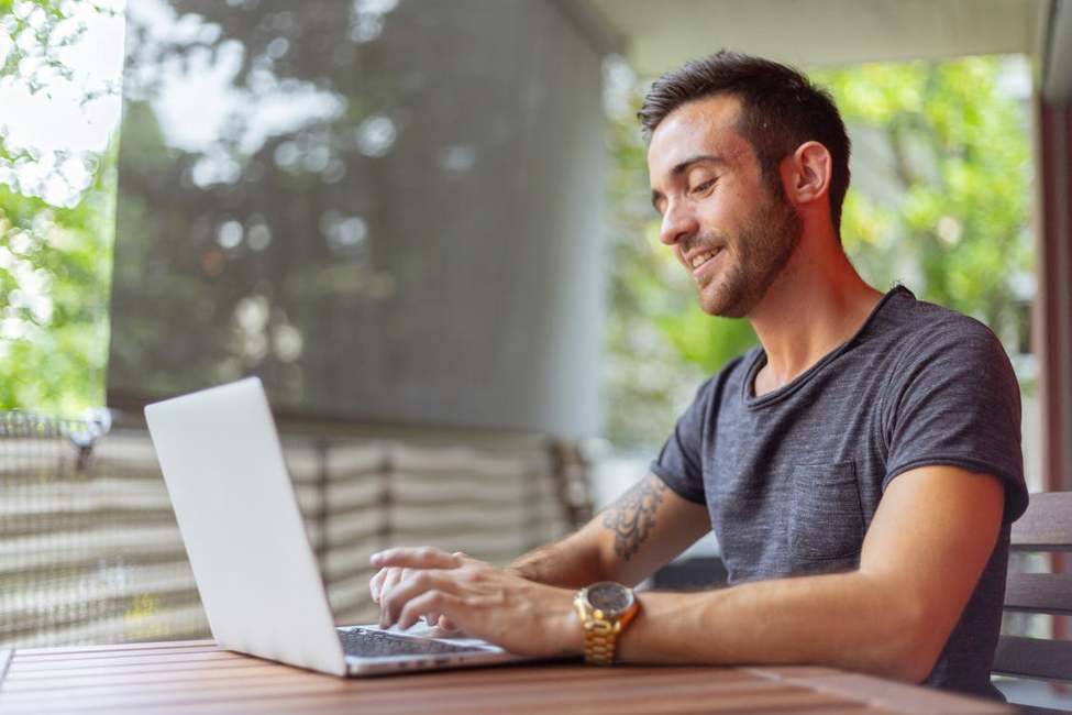 smiling man in gold wrist watch and grey t-shirt researching online installment loan companies on white laptop outside