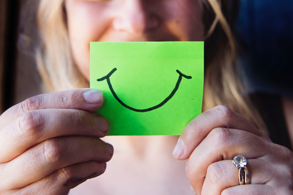woman holding green Post-It note with black smile in front of face
