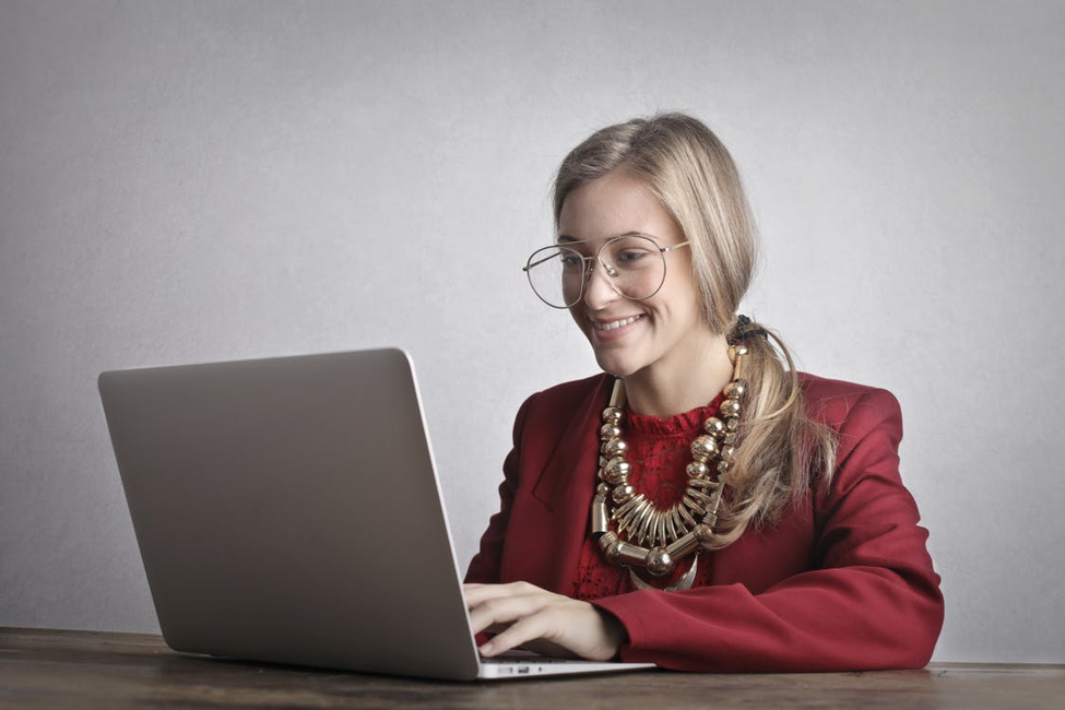 woman in oversized necklace and red blazer smiling resting hands on open laptop in front of grey background