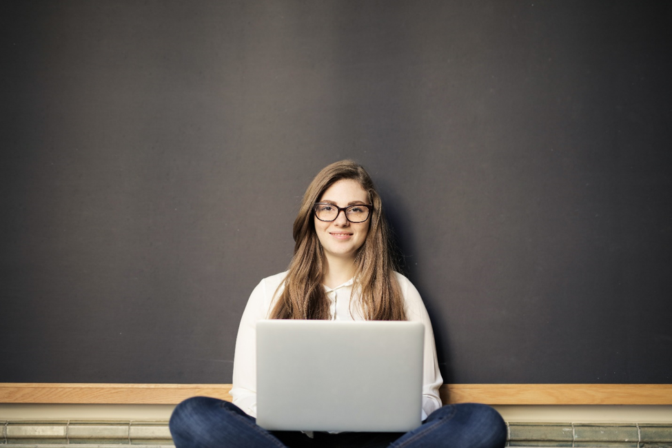 smiling woman wearing glasses sitting cross-legged in front of black board with laptop on her lap, researching online installment loans with monthly payments