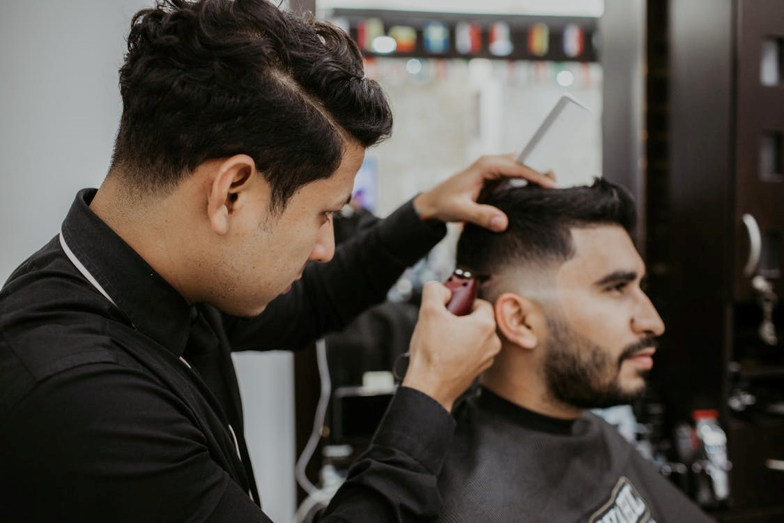 barber in black dress shirt holding comb and hair clippers giving a man with a beard a fade