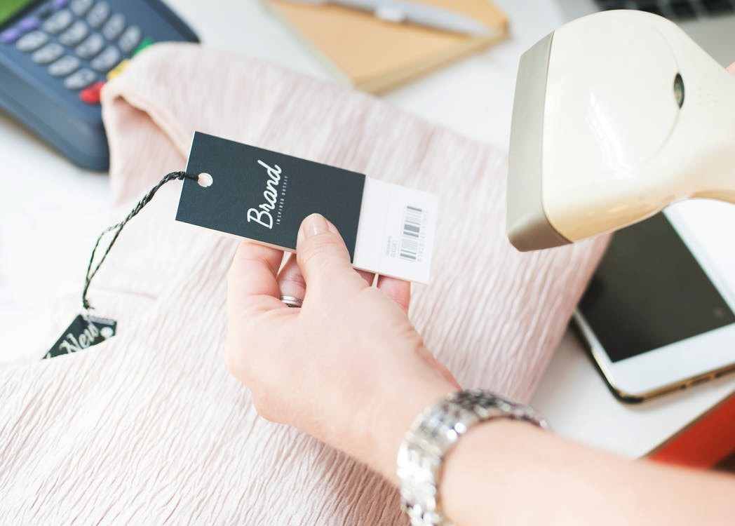 person wearing silver bracelet scanning a barcode tag on a pink shirt