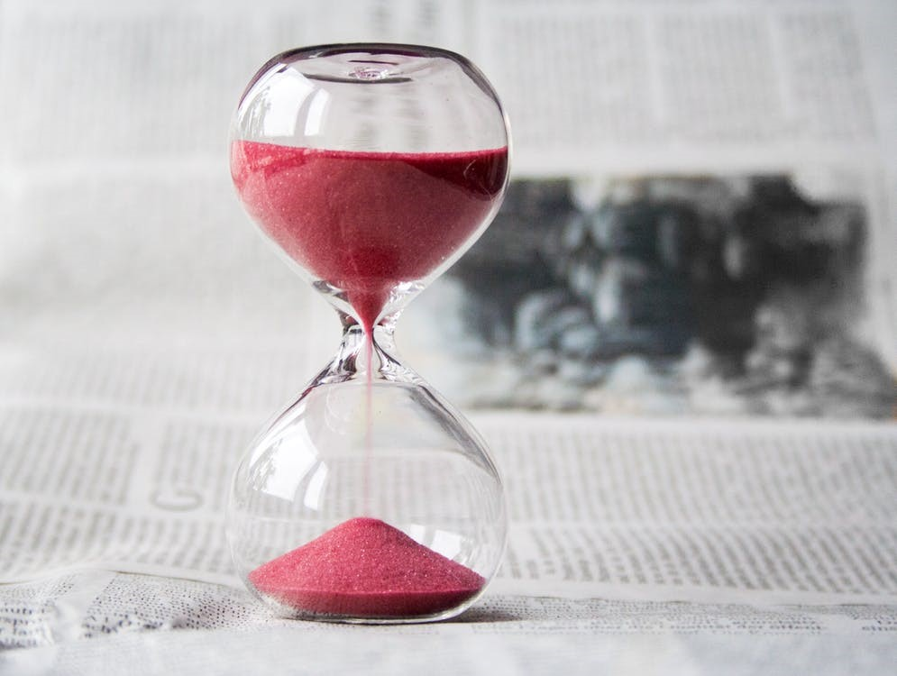 red sand flowing through a glass hour glass on a newspaper